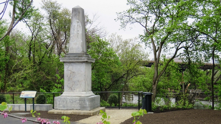 A light gray stone obelisk along the river surrounded by spring foliage