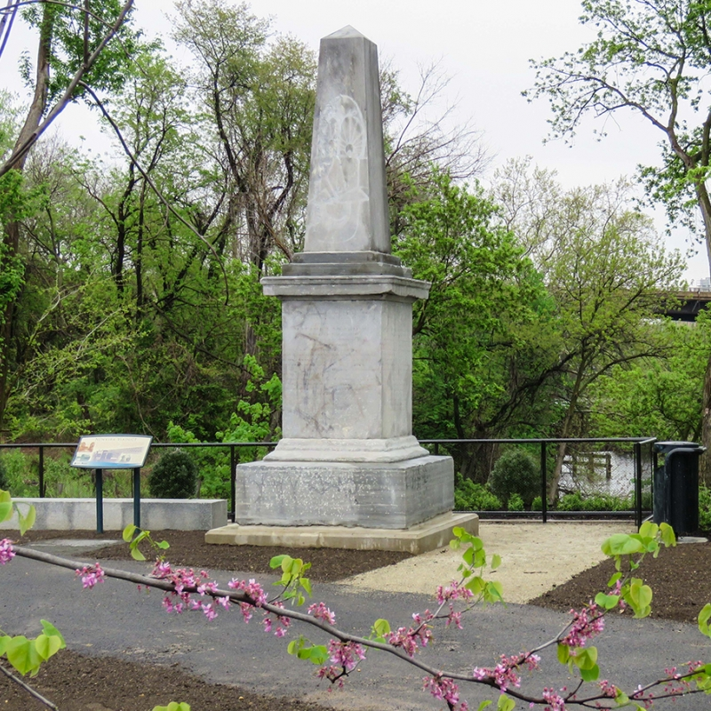 Gray stone obelisk along the river surrounded by spring foliage